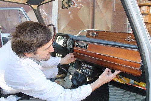 operaio mentre sistema il cruscotto in legno  di un auto d`epoca