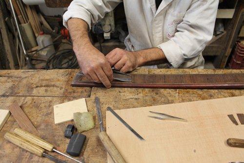 operaio durante la levigazione di un pezzo di legno
