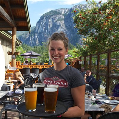 Waitress smiling with tray of beers outside in Squamish