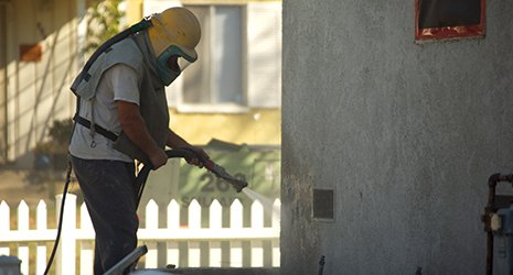 Worker sandblasting at residential home in Rochester