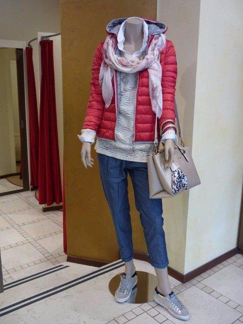 un manichino con un piumino rosso,un foulard,jeans e una borsa beige