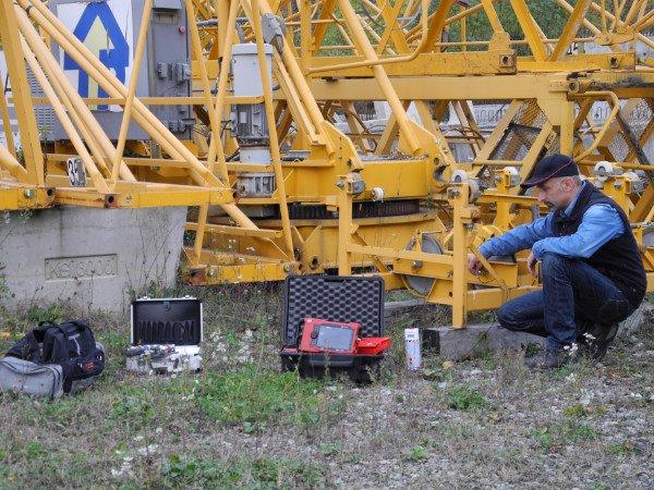un uomo chinato a terra , una valigetta aperta con dentro un dispositivo rosso e dietro delle strutture gialle in ferro