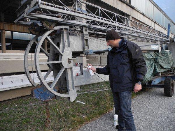 un uomo mentre spruzza un prodotto su una struttura di ferro all'aperto
