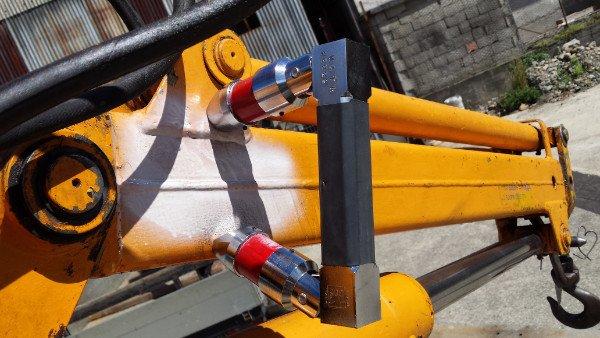 una struttura di ferro di color giallo e in fondo un gancio nero