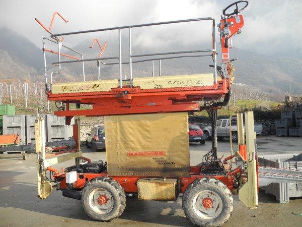 una struttura di ferro di color rosso con delle ruote e sopra una piattaforma con un volante