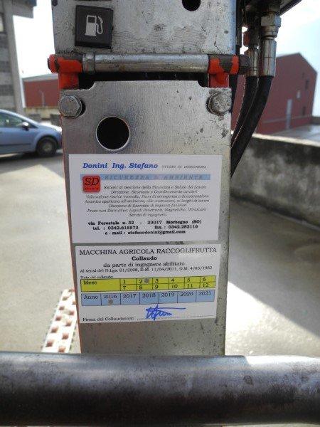 vista di una struttura di ferro con sopra un tasto che raffigura un distributore di benzina e sotto una targhetta che registra l'avvenuto collaudo del macchinario raccoglifrutta