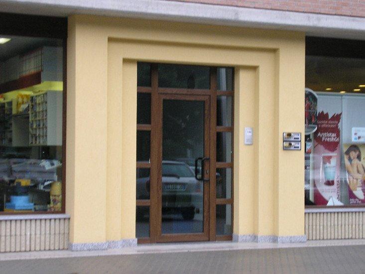 una porta in vetro con finiture in legno di un negozio
