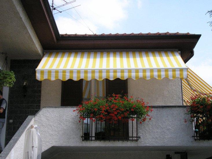una tenda gialla e bianca da esterno in un balcone