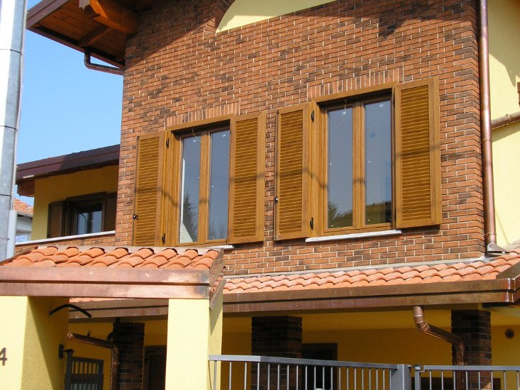 una casa con mattoni a vista e persiane in legno