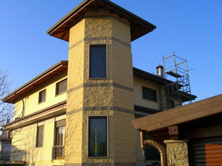 vista di una casa particolare di color giallo con vista delle finestre
