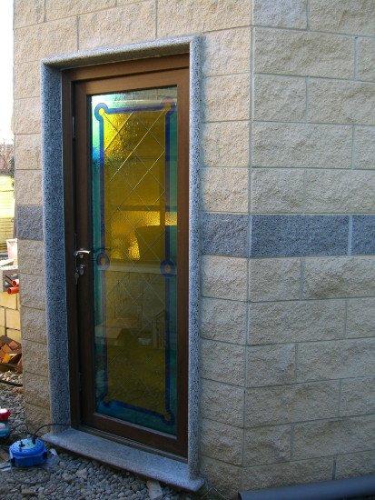 una porta in vetro di diversi colori con finiture in legno