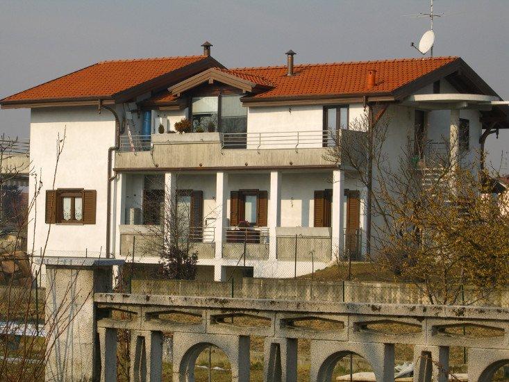 una villa a due piani con delle persiane marroni