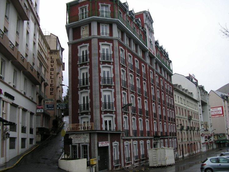 vista di un grande condominio di color bordeaux e un vicolo sulla sinistra