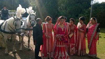 Bride and bridesmaids in red saris beside two horses with white plumage