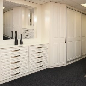 An arrangement of fitted drawers, sliding wardrobes, and a traditional wardrobe