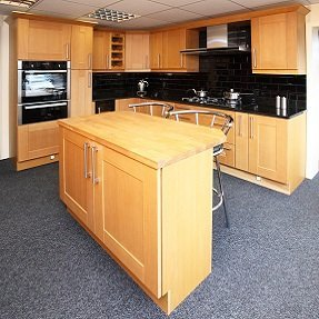 A new kitchen with wooden cabinets and black tops and splashbacks