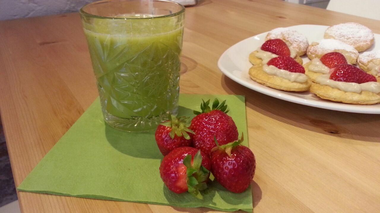 succo di frutta e verdure, dolci e 4 fragole su un tavolo