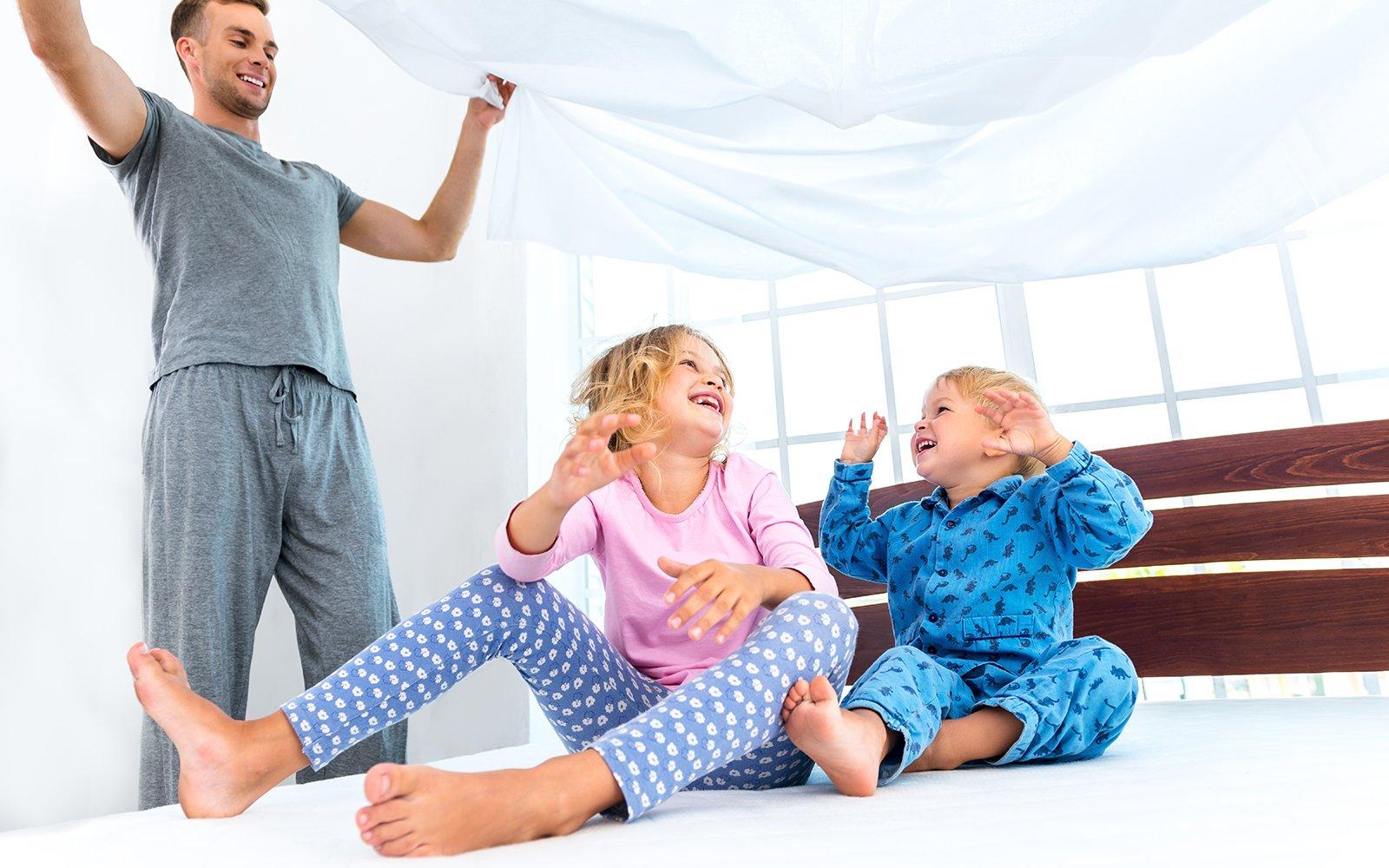 due bambini seduti sul letto e il padre che solleva un lenzuolo