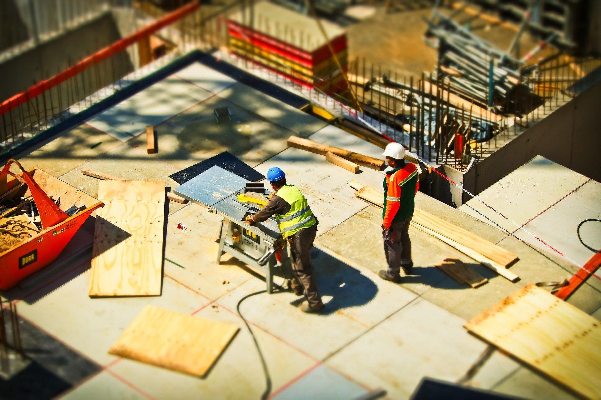 due operai al lavoro in un cantiere con delle assi di legno