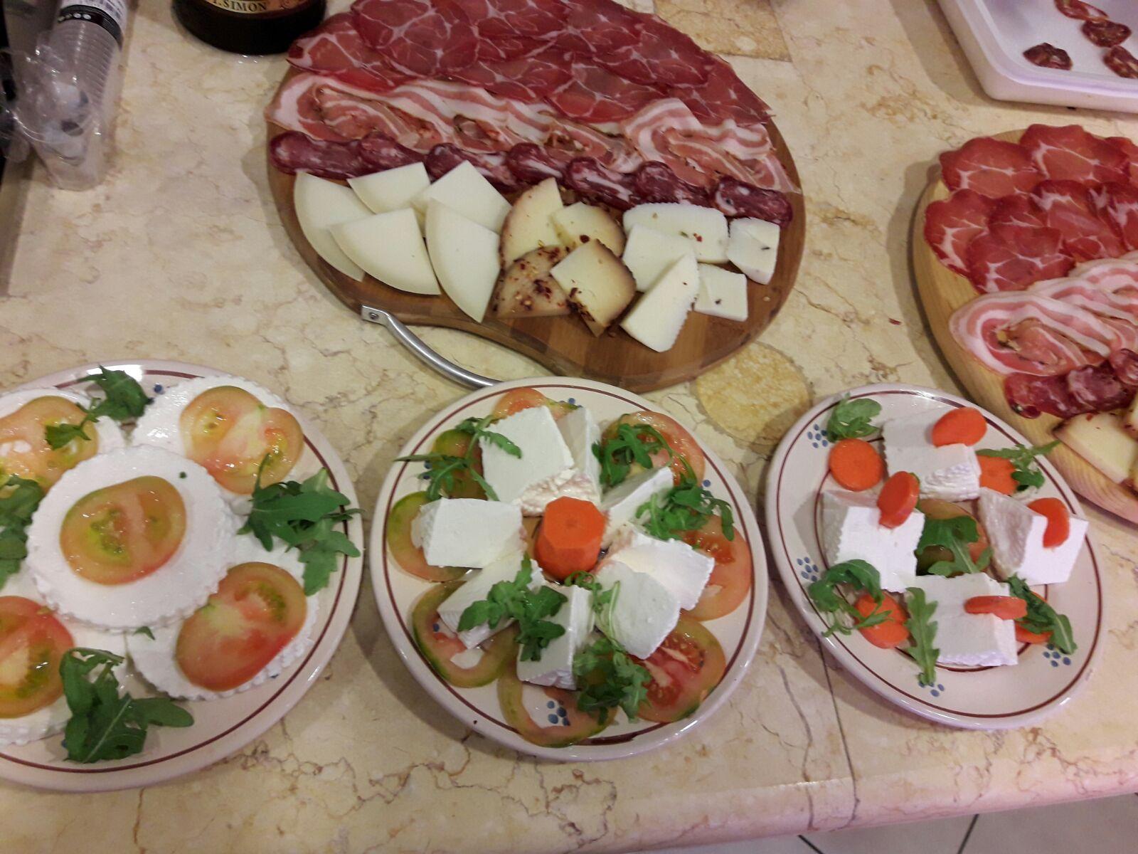 Tagliere di salumi e formaggi, piatti di insalate con formaggi
