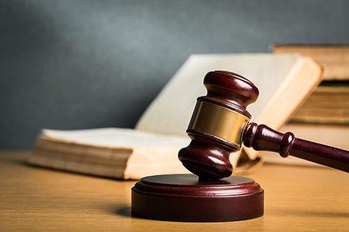 martello del giudice con libro aperto sul tavolo con sfondo grigio