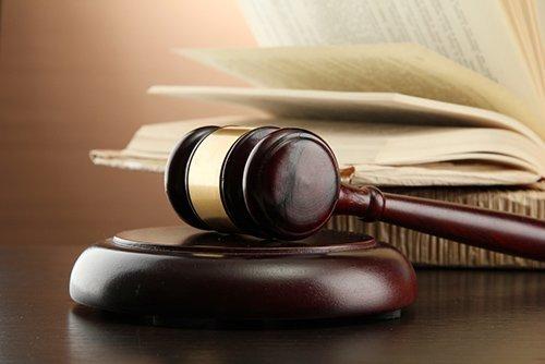 martello del giudice con libro aperto sul tavolo
