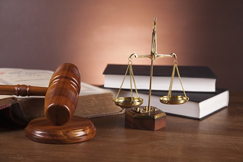 martelletto, bilancia e libri di giudici sul un tavolo