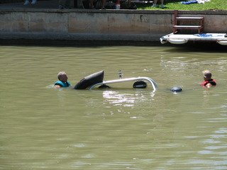 People in the water near sinking boat