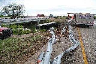 Tractor trailer wreck beneath damaged guardrail