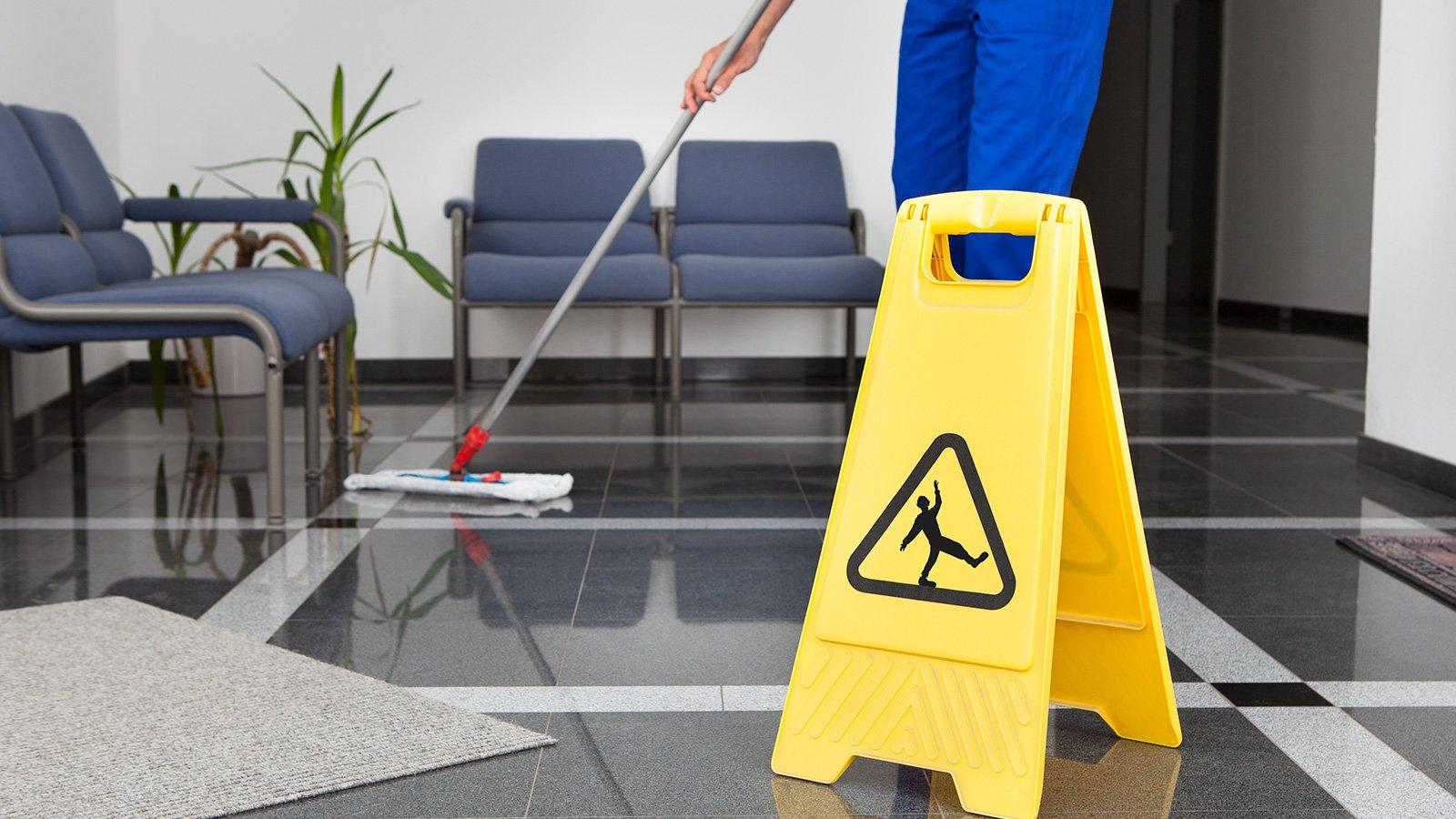 un inserviente che pulisce un pavimento con un mocio in microfibra e un cartello giallo che indica il pericolo di poter scivolare