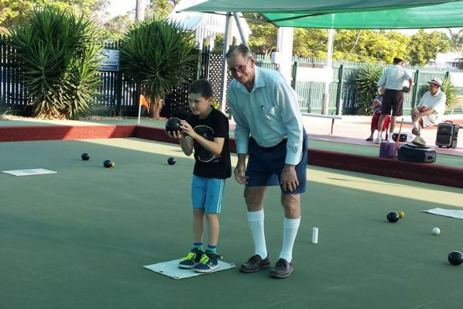family plays lawn bowling game