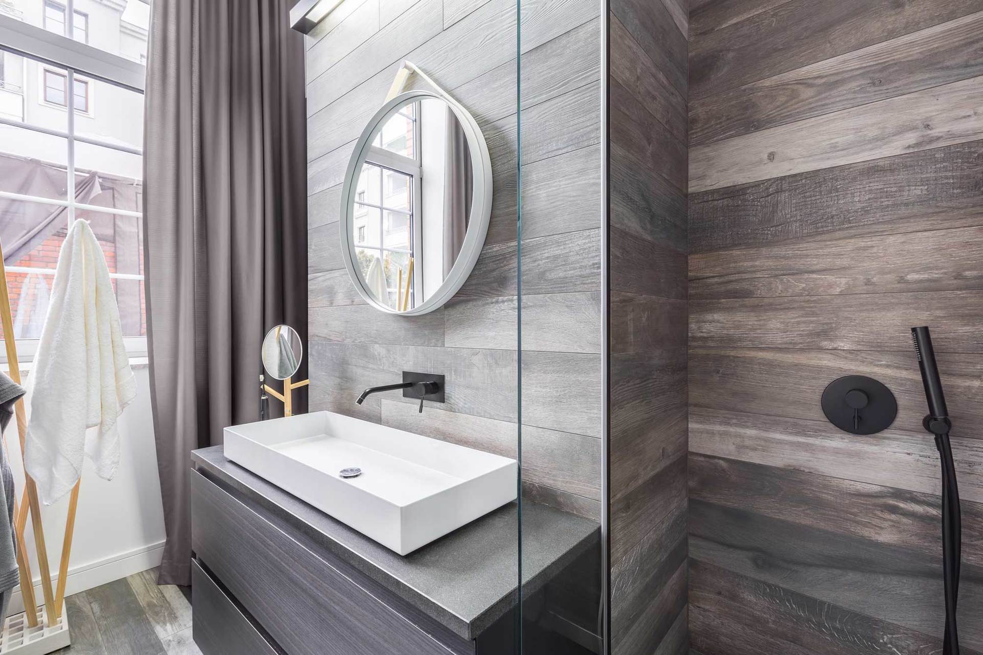 modern bathroom with wall tile and round mirror