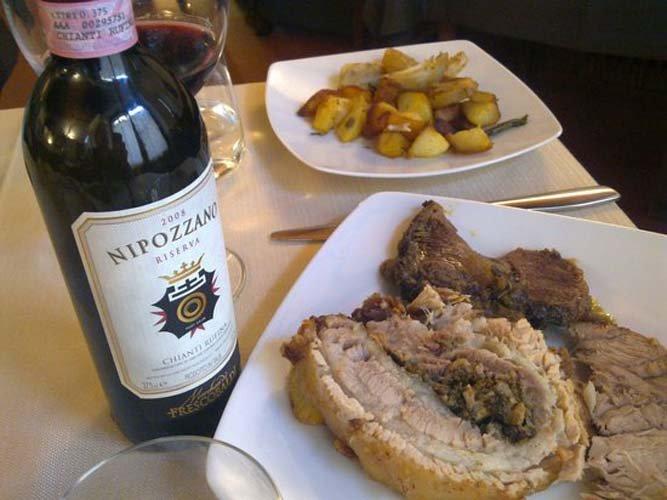 secondo piatto con arrosto patate al forno e bottiglia di vino