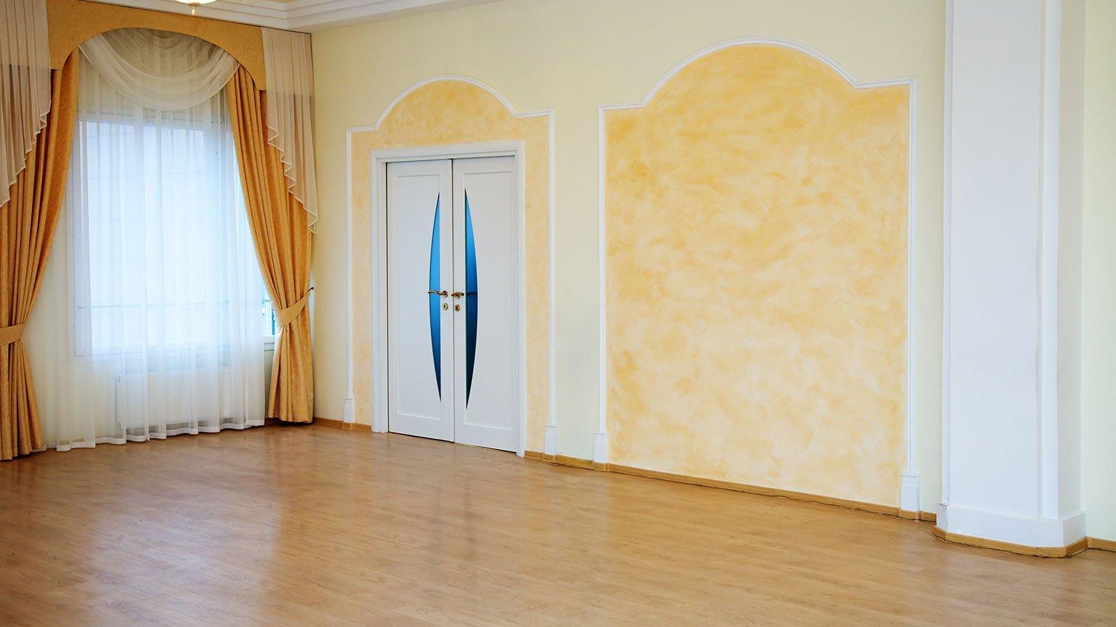 stanza vuota con mura tinteggiate e tenda color oro