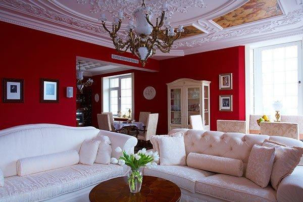 stanza con pareti rosse e decorazioni in gesso al soffitto