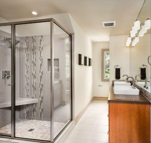 un bagno con un box doccia e un mobile in legno con due lavandini