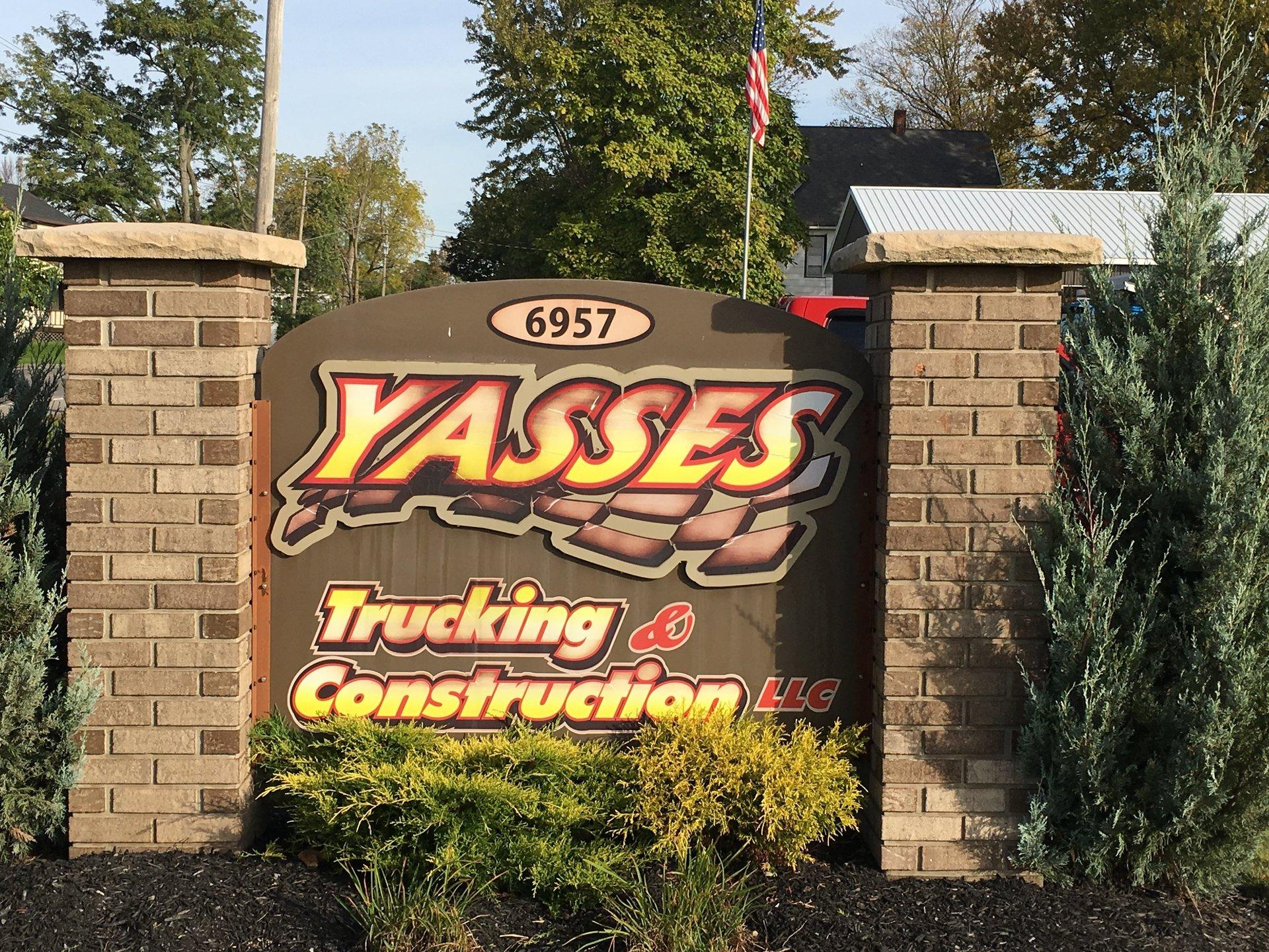 Yasses Trucking & Construction logo on a brick street sign