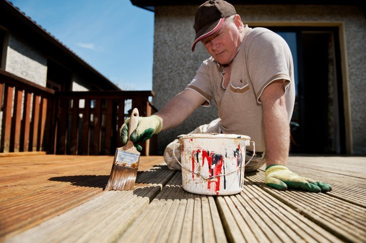 man painting a deck