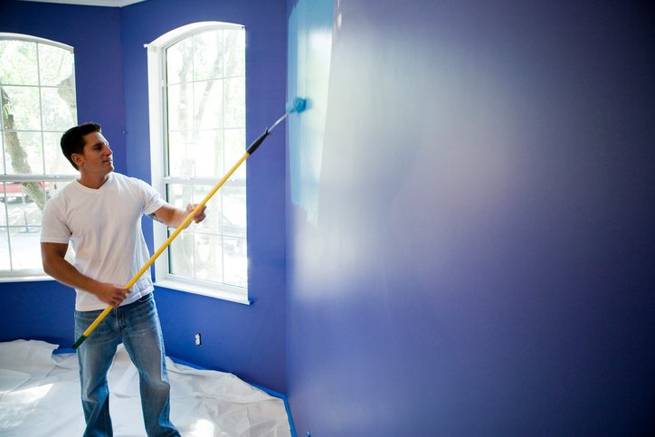 man painting a blue wall