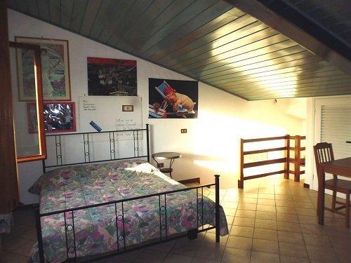 Camera da letto sotto il tetto, ha un letto matrimoniale,tavola e sedie