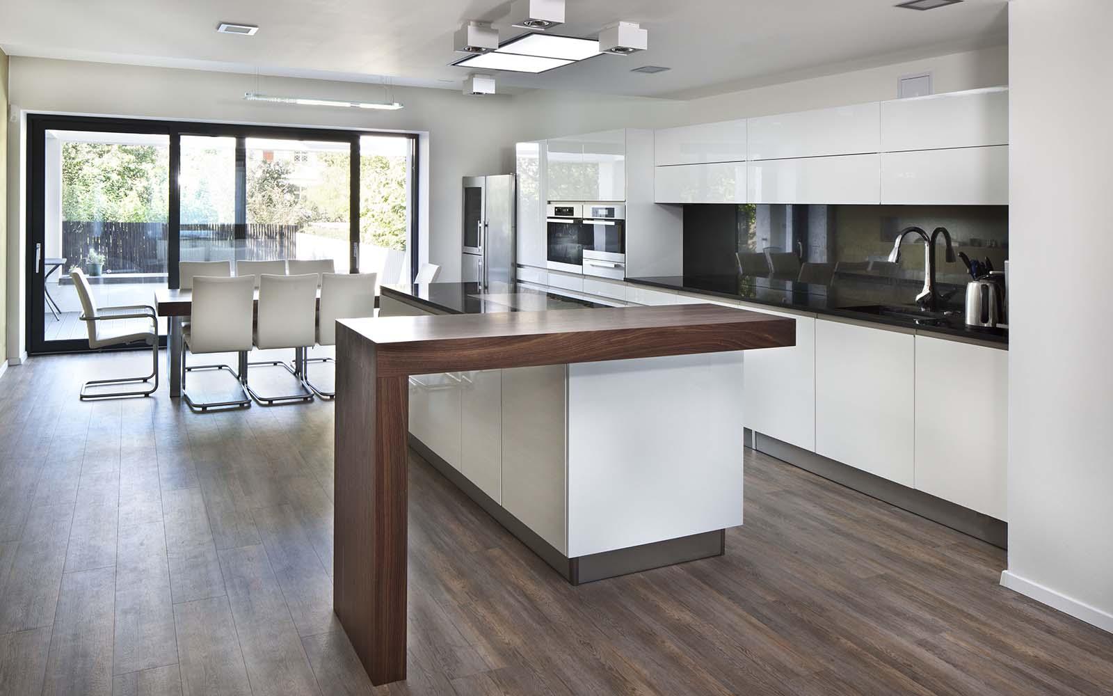 una cucina con dei mobili di color bianco con penisola e l'angolo bar