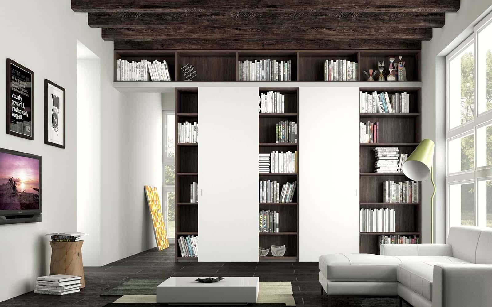 una sala con un divano angolare di color bianco e una libreria in legno