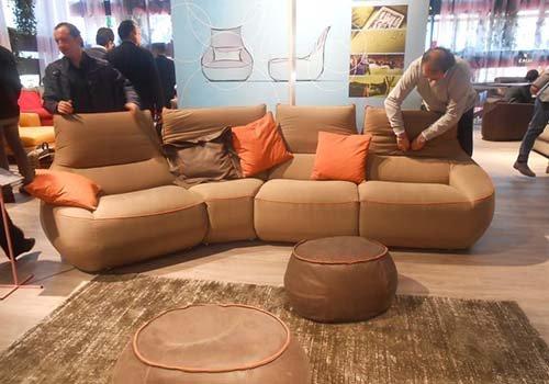 un divano di color beige a quattro posti e due pouf