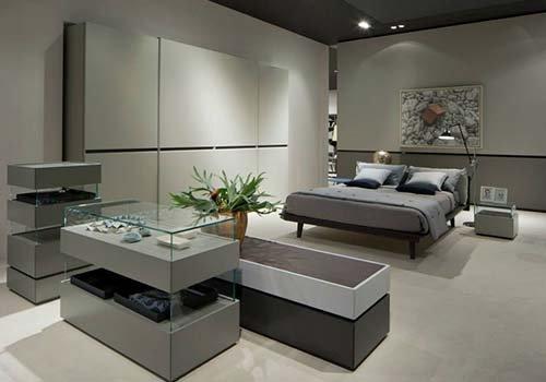 una camera con un letto matrimoniale di color marrone e un armadio di color bianco con delle ante scorrevoli