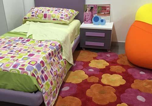 un letto singolo di color viola e un comodino di color grigio e viola