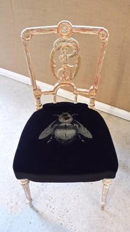 A dining chair with a velvet seat with a bee design on it