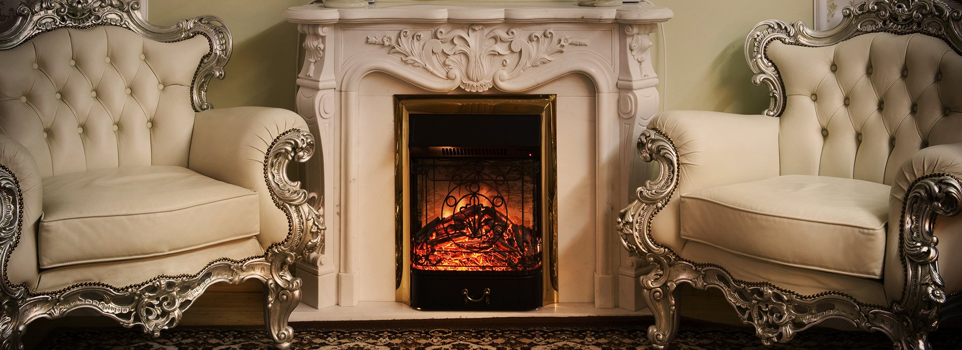 Two cream armchairs with ornate frames on either side of a glowing fireplace with stone surround