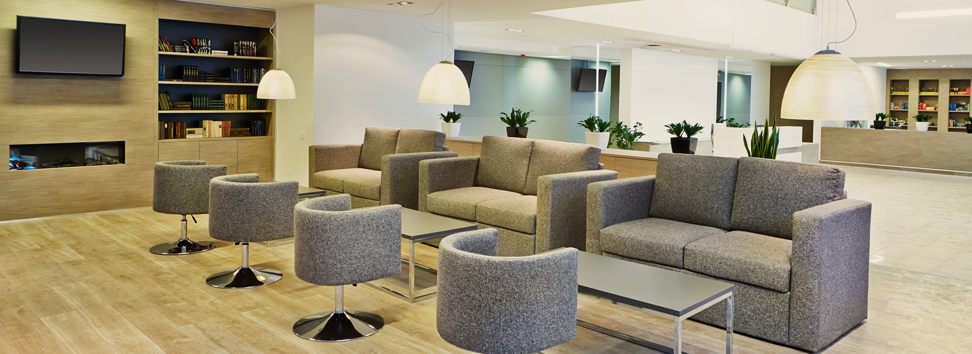 An office space with a large seating area made of grey fabrics