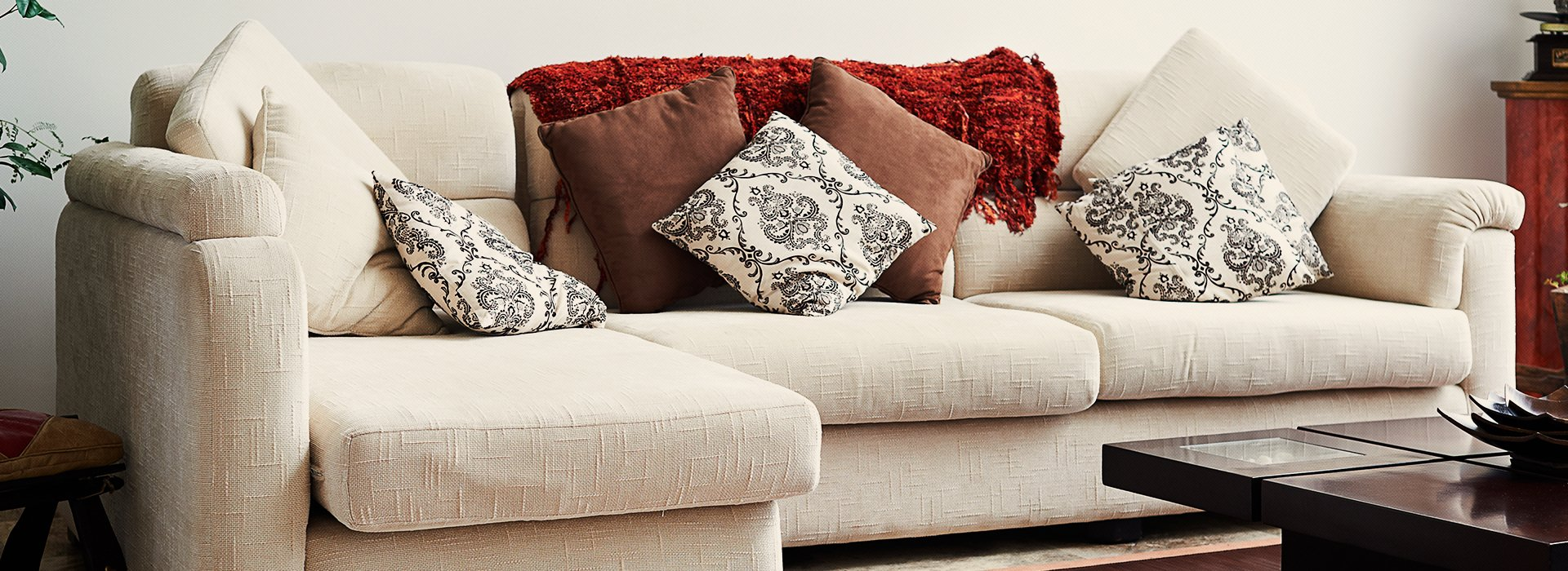 A cream corner sofa with contrasting cushions and russet coloured throw