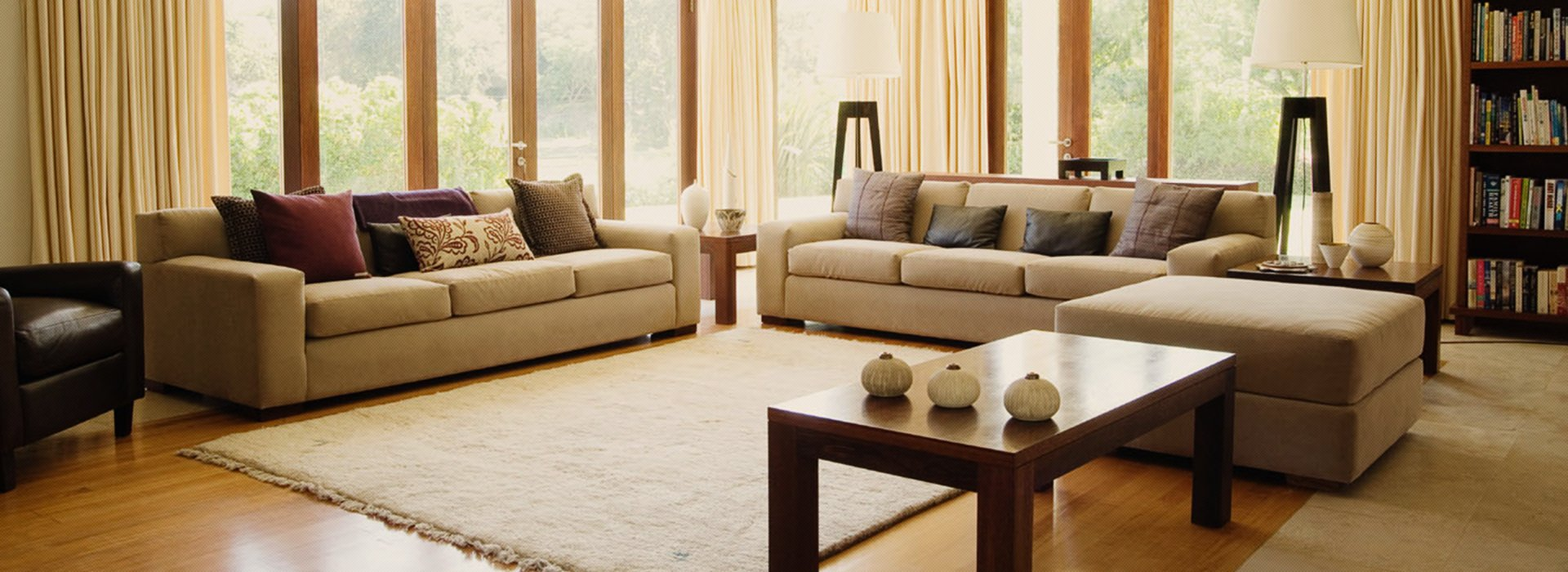 Two long beige sofas at right angles in a corner window around a cream rug, with a wooden coffee table and large stool matching the sofas
